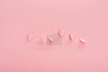 Photo pour Top vue des cœurs en papier rose sur fond rose - image libre de droit