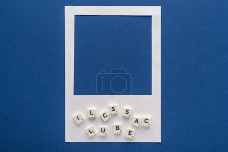 Photo for Top view of letters on cubes and white photo frame on blue background - Royalty Free Image