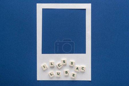Photo pour Vue du haut des lettres sur cubes et cadre photo blanc sur fond bleu - image libre de droit