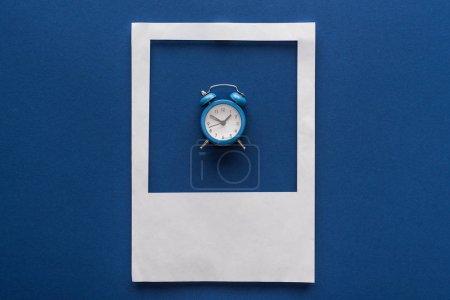 Ansicht des Weckers in weißem Fotorahmen auf blauem Hintergrund