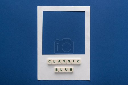 top view of classic blue lettering on cubes on white photo frame on blue background