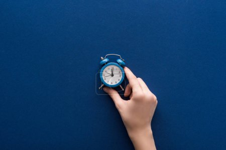 Photo for Cropped view of woman holding small alarm clock on blue background - Royalty Free Image