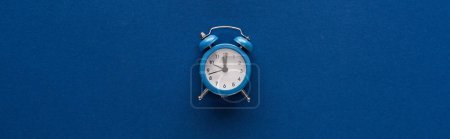 Photo for Top view of alarm clock on blue background, panoramic shot - Royalty Free Image
