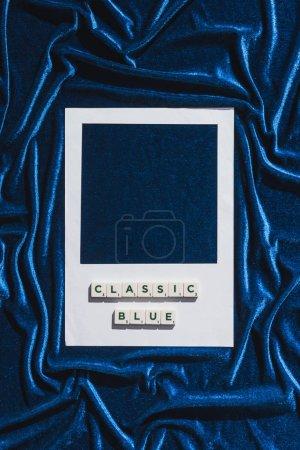 Photo pour Vue de dessus du lettrage bleu classique sur cubes et cadre photo blanc sur tissu velours bleu - image libre de droit