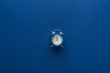 Photo for Top view of alarm clock on blue background - Royalty Free Image