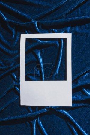Photo pour Vue du dessus du cadre photo blanc vide sur tissu velours bleu - image libre de droit