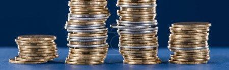 piles de pièces d'argent et d'or en métal sur fond bleu, plan panoramique