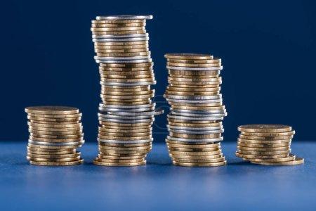 Photo pour Piles de métal argent et pièces d'or sur fond bleu - image libre de droit