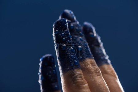 Photo pour Vue rapprochée de la main féminine avec doigts peints mouillés isolés sur bleu - image libre de droit