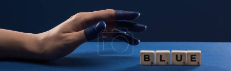 Photo pour Vue recadrée de la main féminine avec les doigts peints près des cubes avec lettrage bleu isolé sur bleu, prise de vue panoramique - image libre de droit
