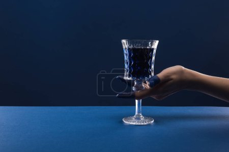 Photo for Cropped view of female hand with painted fingers holding faceted glass with drink isolated on blue - Royalty Free Image