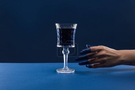 cropped view of female hand with painted fingers near faceted glass with drink isolated on blue