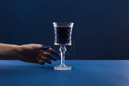 abgeschnittene Ansicht der weiblichen Hand mit bemalten Fingern in der Nähe facettiertes Glas mit Getränk isoliert auf blau