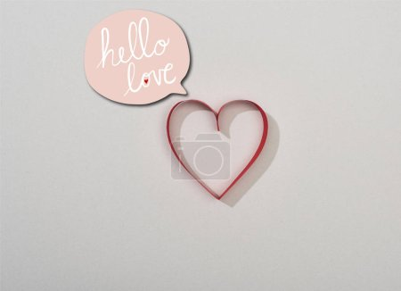 Photo pour Haut de la page coeur de papier rouge sur fond gris avec bonjour lettrage d'amour dans la bulle de la parole - image libre de droit