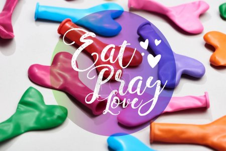 Photo for Colorful heart shaped balloons on grey background with eat, pray, love lettering - Royalty Free Image