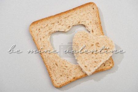 Photo pour Vue du dessus de tranche de pain avec coeur sculpté et être le mien lettrage Saint-Valentin sur fond gris - image libre de droit