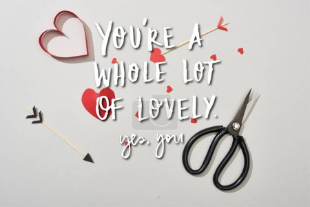 Photo for Top view of heart shaped papers with arrows and scissors on grey background with you are a whole lot of lovely lettering - Royalty Free Image