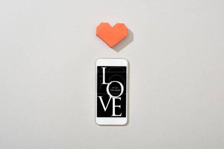 Photo pour Vue du dessus du smartphone avec mot d'amour et coeur en papier sur fond gris - image libre de droit