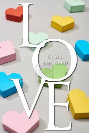Photo pour Coeurs multicolores décoratifs sur fond gris avec amour est tout ce dont vous avez besoin d'illustration - image libre de droit
