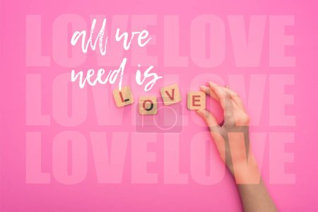Photo for Partial view of woman holding cubes with all we need is love lettering on pink background - Royalty Free Image