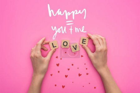 partial view of woman holding cubes with love lettering on pink background with happy you and me illustration