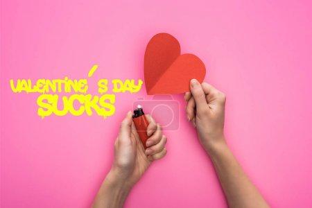 Photo pour Vue en coupe d'une femme allumant un cœur de papier rouge vide avec un briquet isolé sur rose avec des valentins illustration de sucettes de jour - image libre de droit