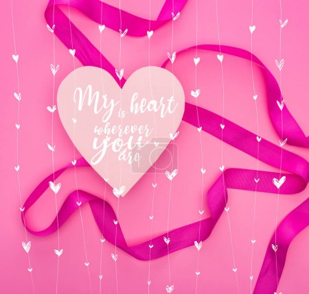 Photo pour Top view of paper heart with my heart is wherever you are illustration and ribbon isolated on pink - image libre de droit
