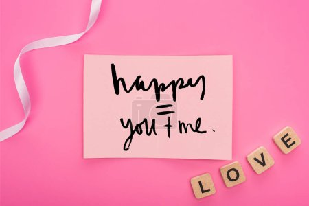 Photo for Top view of empty paper card with happy you and me lettering near ribbon and love lettering on wooden cubes isolated on pink - Royalty Free Image