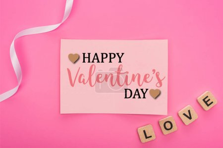 Photo for Top view of empty paper card with  happy valentines day lettering near ribbon and love lettering on wooden cubes isolated on pink - Royalty Free Image