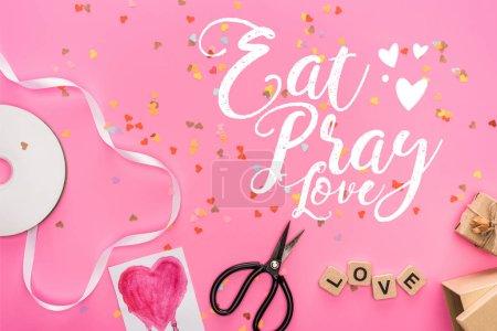 Photo pour Vue du dessus des confettis de Saint-Valentin, disque compact vide, ciseaux, boîtes-cadeaux, carte de voeux et lettrage d'amour sur des cubes en bois sur fond rose avec manger, prier, lettrage d'amour - image libre de droit