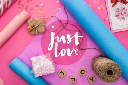Foto de Vistas superiores de la decoración, papel de envolver, gemelos, cajas de regalo, carta de felicitación y carta de amor en cubos de madera de fondo rosa con sólo el amor de la carta de presentación. - Imagen libre de derechos