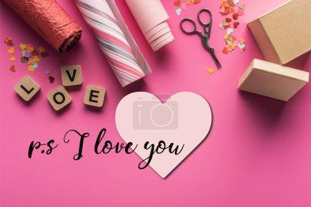 Photo pour Vue de dessus de décoration de valentines, ciseaux, boîte cadeau, papier d'emballage et lettrage d'amour sur des cubes en bois sur fond rose avec coeur et ps je vous aime lettrage - image libre de droit