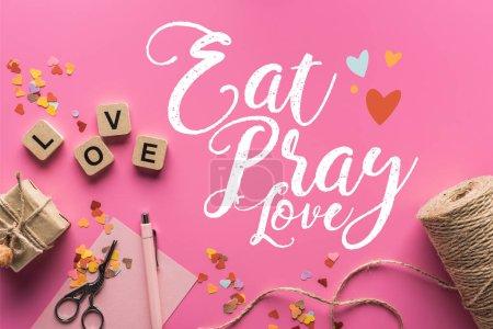 Photo pour Vue de dessus de décoration de valentines, ciseaux, boîte cadeau, ficelle et lettrage d'amour sur cubes en bois sur fond rose avec manger, prier, lettrage d'amour - image libre de droit