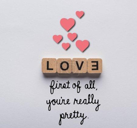 Photo pour Vue du haut des cubes avec des lettres d'amour sur fond blanc avec tout d'abord vous êtes vraiment joli lettrage et illustration des cœurs - image libre de droit