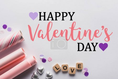 Photo for Top view of silver hearts, wrapping paper and cubes with love lettering on white background with happy valentines day illustration - Royalty Free Image