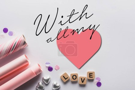 Photo for Top view of silver hearts, wrapping paper and cubes with love lettering on white background with all my lettering and heart illustration - Royalty Free Image