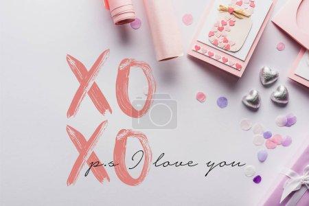 Photo pour Vue du dessus de décoration de valentines, cadeaux, coeurs et papier d'emballage sur fond blanc avec xoxo ps i love you lettering - image libre de droit