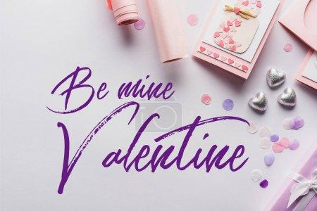 Photo pour Vue du dessus de la décoration de la Saint-Valentin, cadeaux, coeurs et papier d'emballage sur fond blanc avec être le mien lettrage Saint-Valentin - image libre de droit