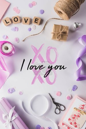 Photo pour Vue du dessus de la décoration des valentines, des cadeaux, des fournitures artisanales et des lettres d'amour sur cubes sur fond blanc avec xoxo je t'aime illustration - image libre de droit