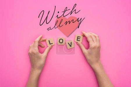 Photo pour Vue partielle de la femme tenant des cubes avec des lettres d'amour sur fond rose avec tous mes lettrages - image libre de droit