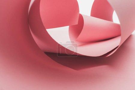rosa Papierwirbel mit Schatten isoliert auf weiß