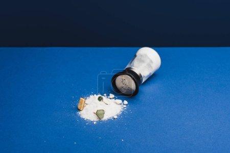 Pierścienie biżuterii z kamieni szlachetnych na soli przez solniczkę na klasycznej niebieskiej powierzchni