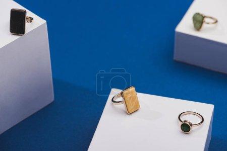 Photo pour Vue en gros plan des anneaux de bijoux sur cubes blancs sur fond bleu - image libre de droit