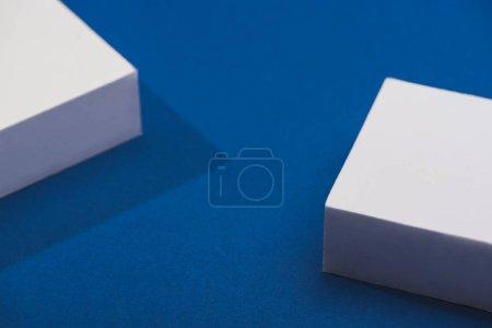 Photo pour Vue grand angle des cubes blancs avec ombre sur fond bleu - image libre de droit