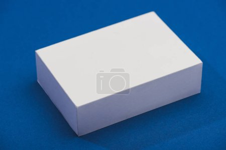 High angle view of white stand with shadow on blue background