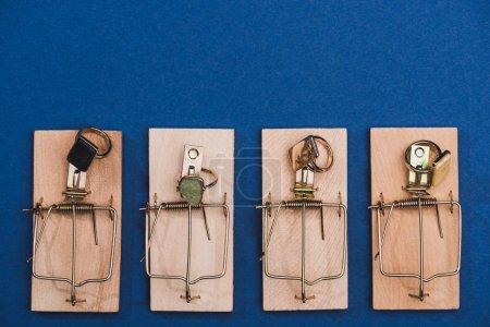 Photo pour Vue en haut des anneaux de bijoux dans des pièges à souris sur fond bleu - image libre de droit