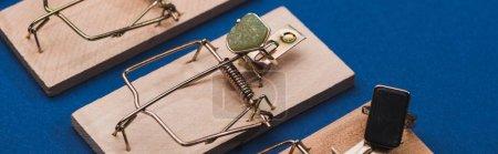 Photo pour Vue panoramique des bagues à bijoux avec des pierres précieuses dans les pièges à souris sur la surface bleue - image libre de droit