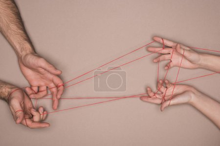 Top view of man and woman holding red string on beige background
