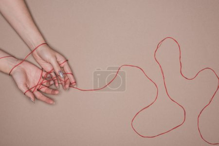 Top view of female hands wrapped in red string on beige background
