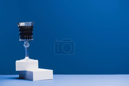 Photo pour Verre à vin avec liquide bleu sur blocs sur fond bleu classique - image libre de droit